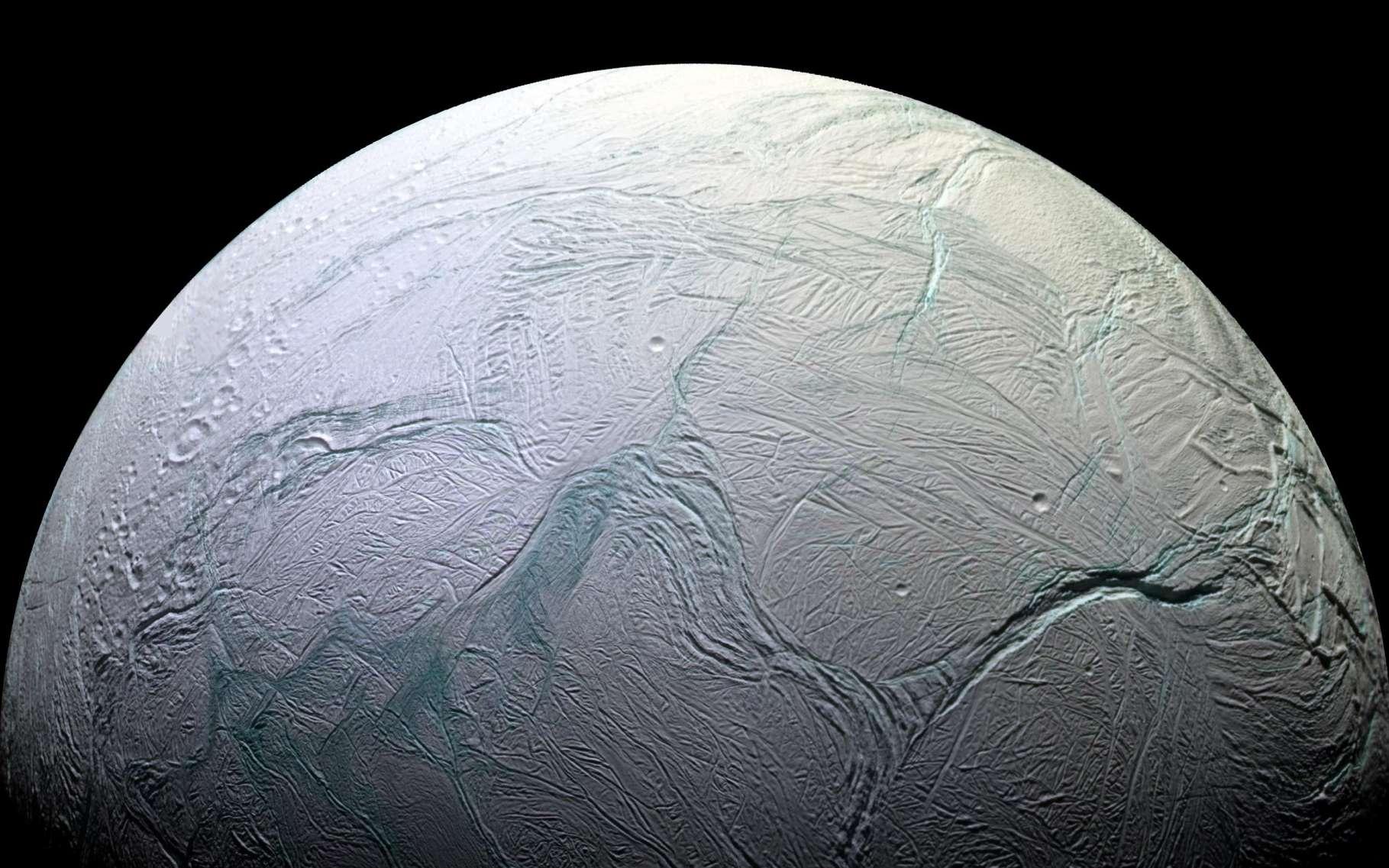 Encelade, un des satellites de Saturne, photographié par la sonde Cassini. Sa surface de glace cache des masses d'eau liquide. Dans ce monde froid, la chaleur vient du malaxage de cette lune par la gravité de la géante gazeuse. L'étude fine de ses mouvements permet de mieux comprendre à la fois Encelade et Saturne. © Nasa