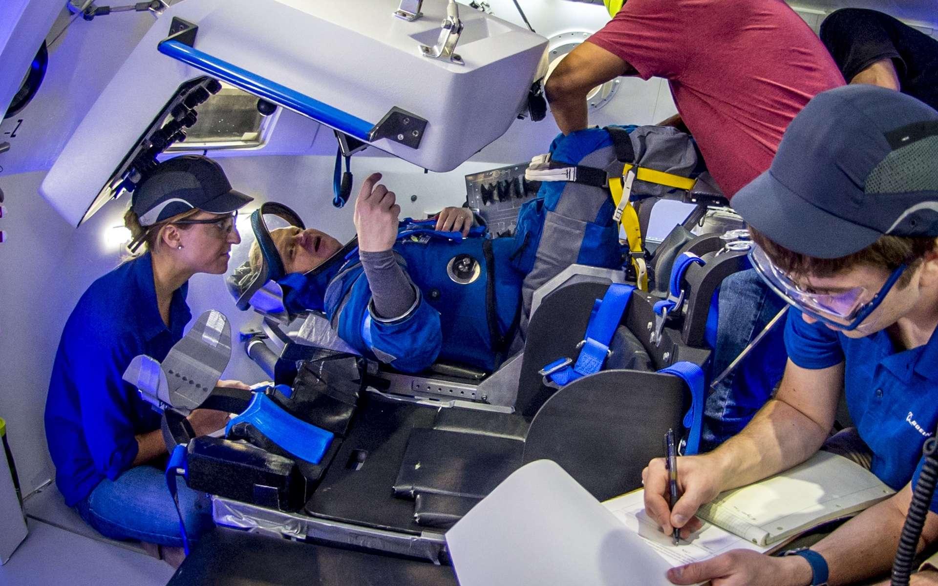 L'astronaute Eric Boe teste la nouvelle combinaison spatiale de Boeing à l'intérieur d'une maquette du cockpit de la future capsule Starliner. © Boeing