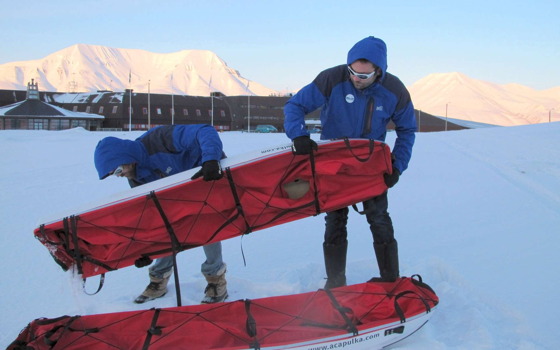 Le 26 mars 2012 : Alan Le Tressoler (à gauche) et Julien Cabon devant l'université de Longyearbyen, au Spitzberg. Ils viennent de recevoir leurs traîneaux de 2,20 mètres qui serviront à leur expédition au pôle Nord. Commentaire d'Alan Le Tressoler : « On prépare les traîneaux... Pour des luges ça paraît grand, mais pour un déménagement au pôle Nord, y'a rien de trop ! ». © Pôle Nord 2012