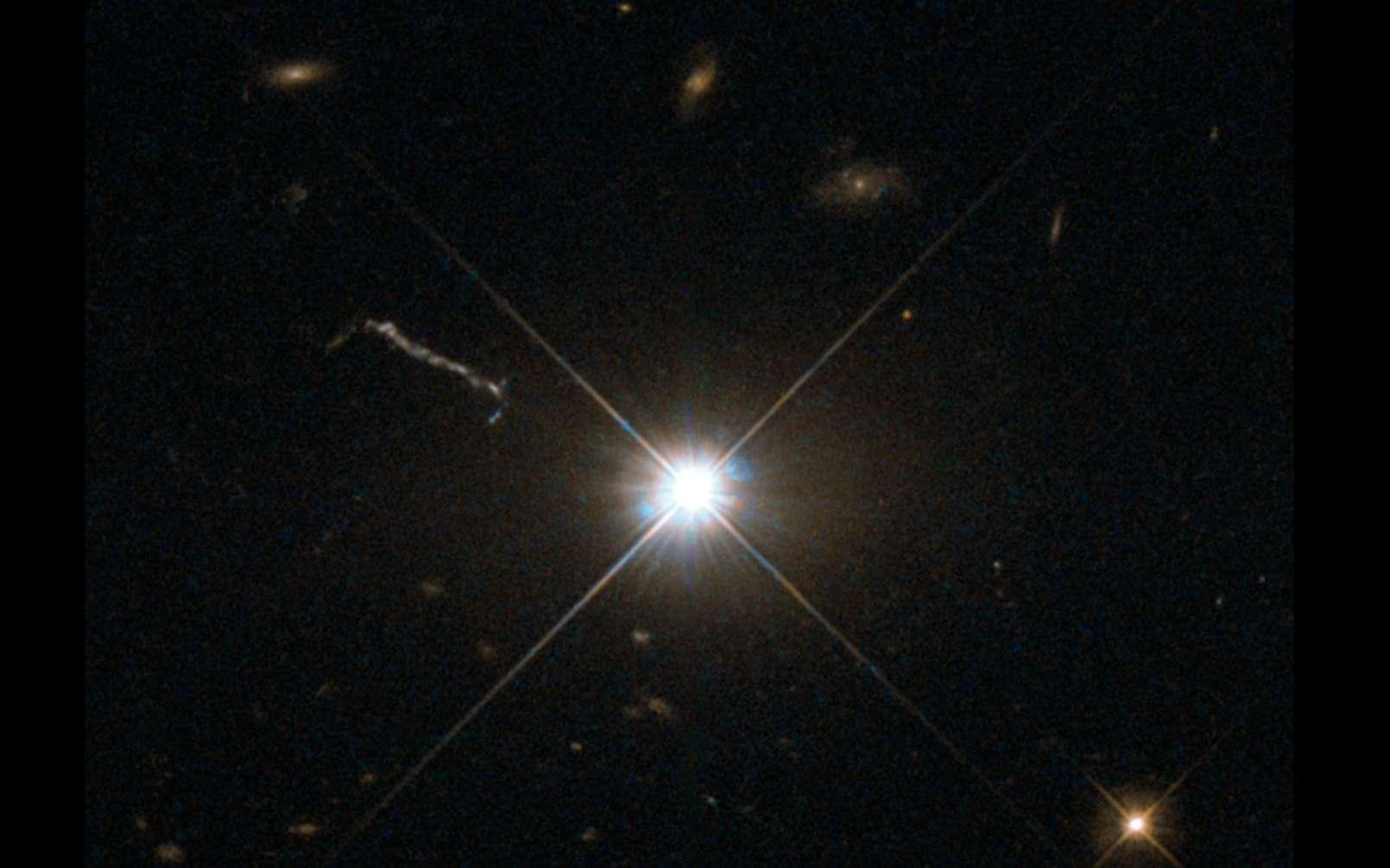 Image optique du quasar 3C 273, obtenue avec le télescope spatial Hubble. Le quasar réside au cœur d'une galaxie elliptique géante de la constellation de la Vierge, à une distance d'environ 2,5 milliards d'années-lumière. Un jet de matière provenant des régions centrales de la galaxie est visible à gauche de l'image. © CNRS, ESA, Hubble & Nasa