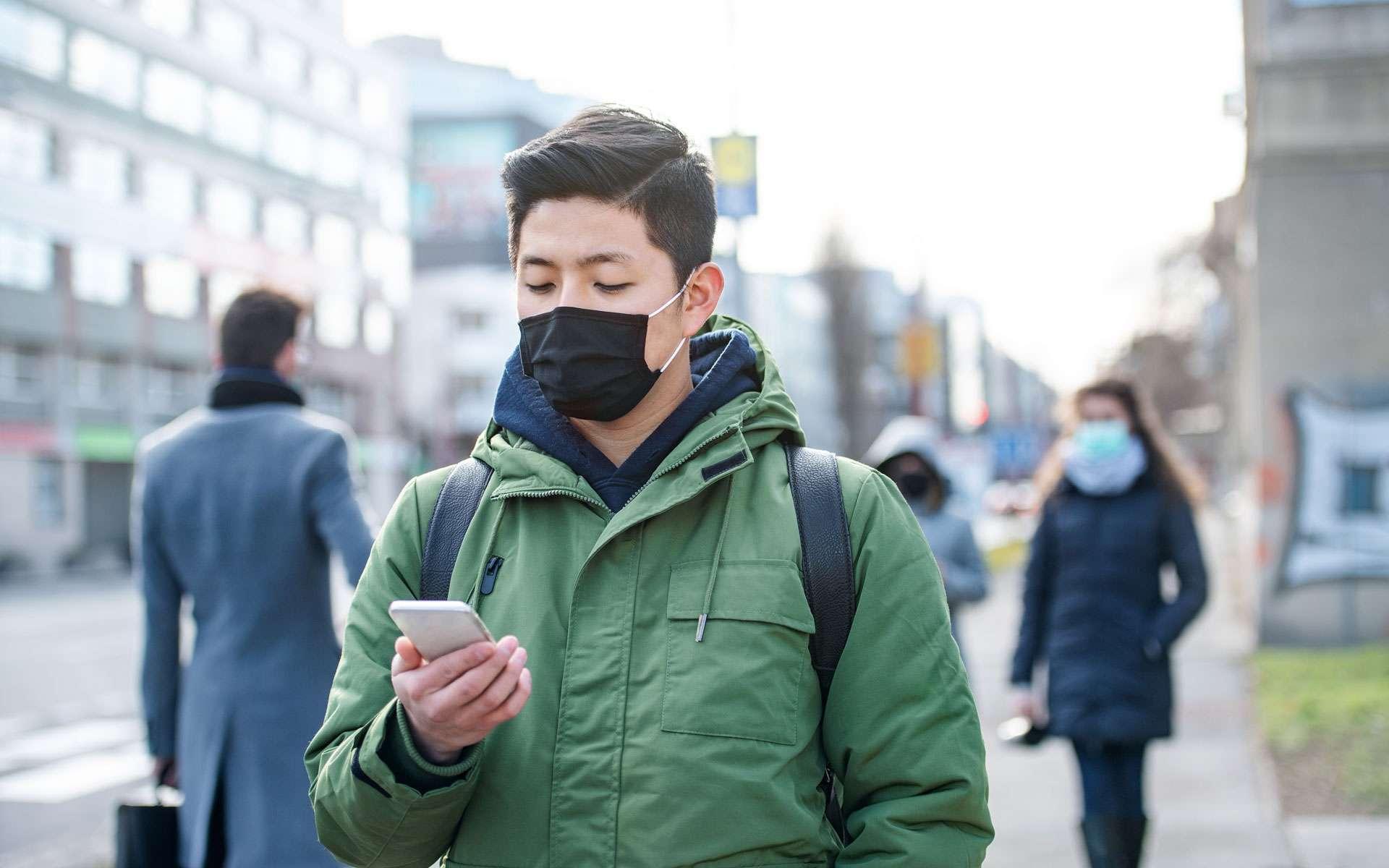 Un homme masqué se balade dans la rue, téléphone en main. ©halfpoint, Envato elements