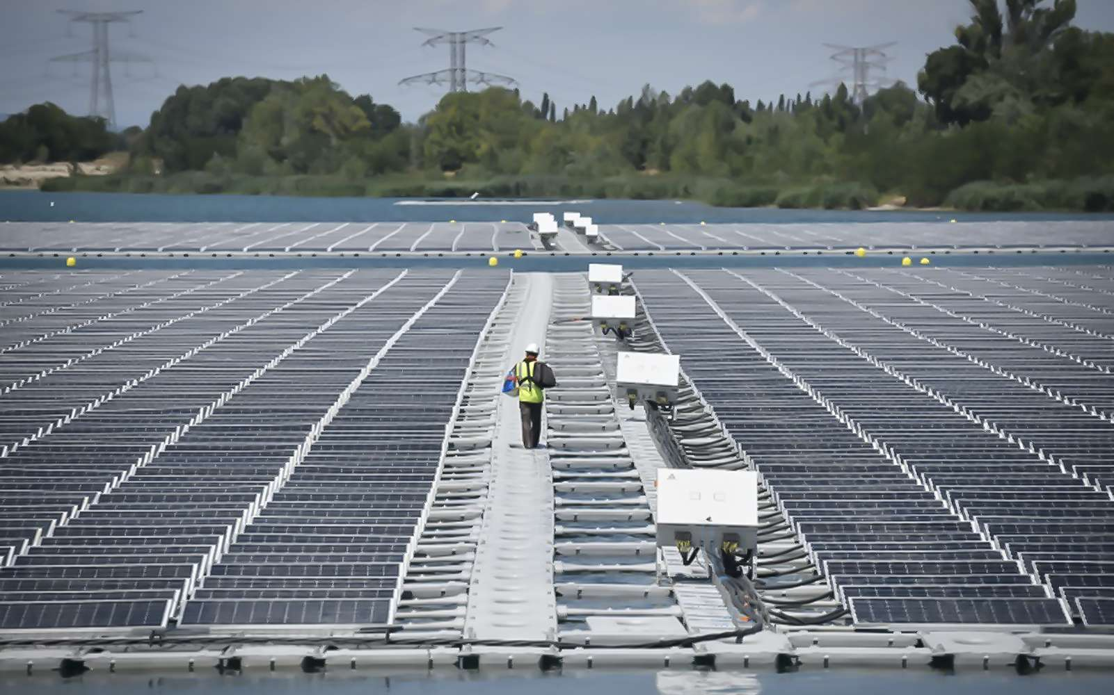 Un technicien marche entre les panneaux photovoltaïque de la centrale flottante O'Megal, le 30 juillet 2019 à Piolenc, dans le Vaucluse. © Gérard Julien, AFP