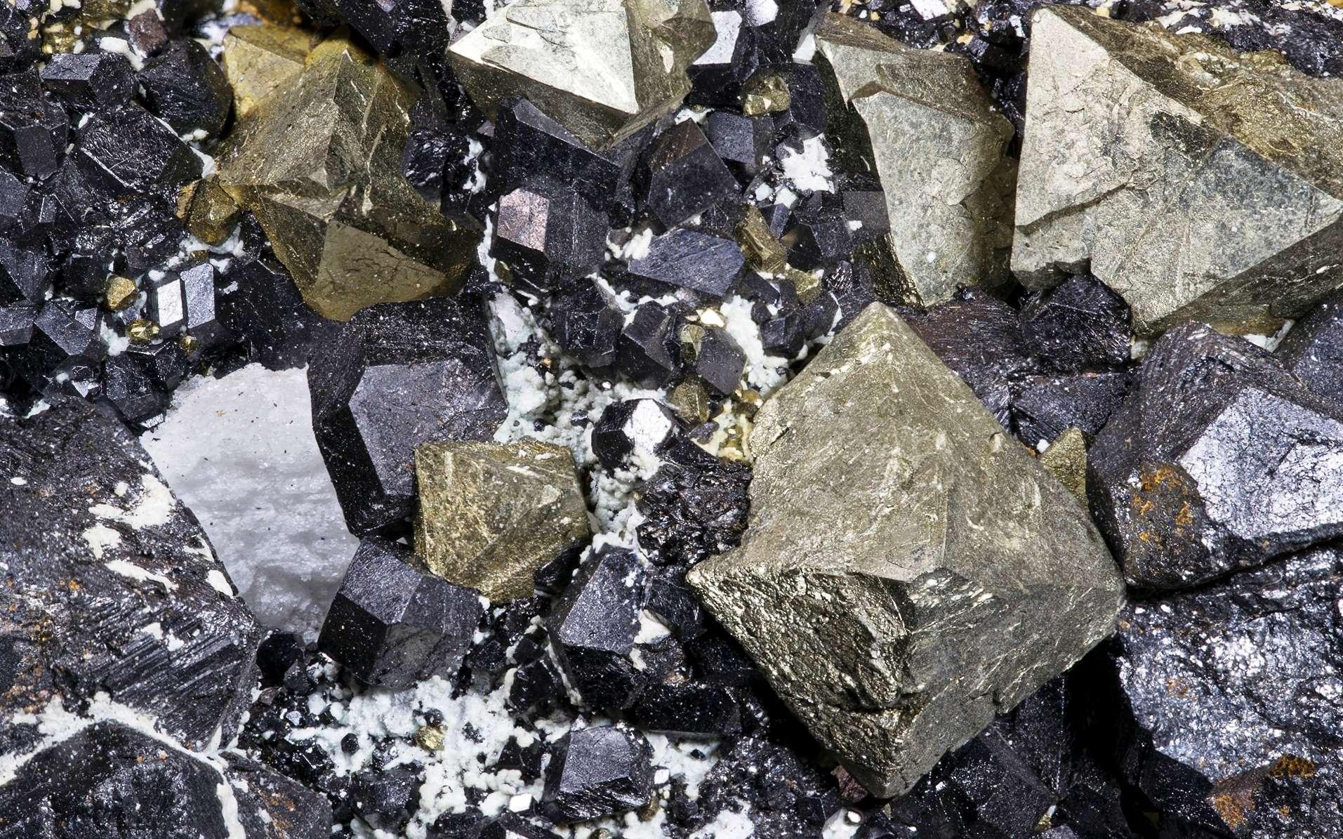 Groupe de cristaux de magnétite en rhombododécaèdre avec cristaux de pyrite octaédriques (jaunes). La magnétite est un exemple de matériau ferromagnétique. © Archaeodontosaurus, Wikipédia, cc by sa 3.0
