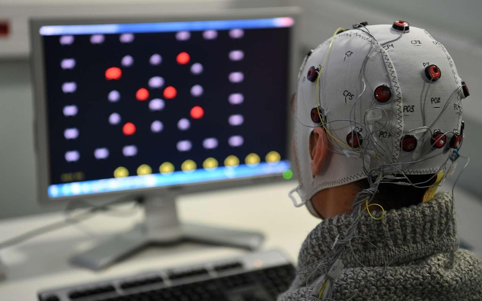 Une personne équipée d'un casque EEG essaie le jeu Brain Invaders développé par le laboratoire images parole signal automatique (GIPSA-lab) de Grenoble. © Jean-Pierre Clatot / AFP