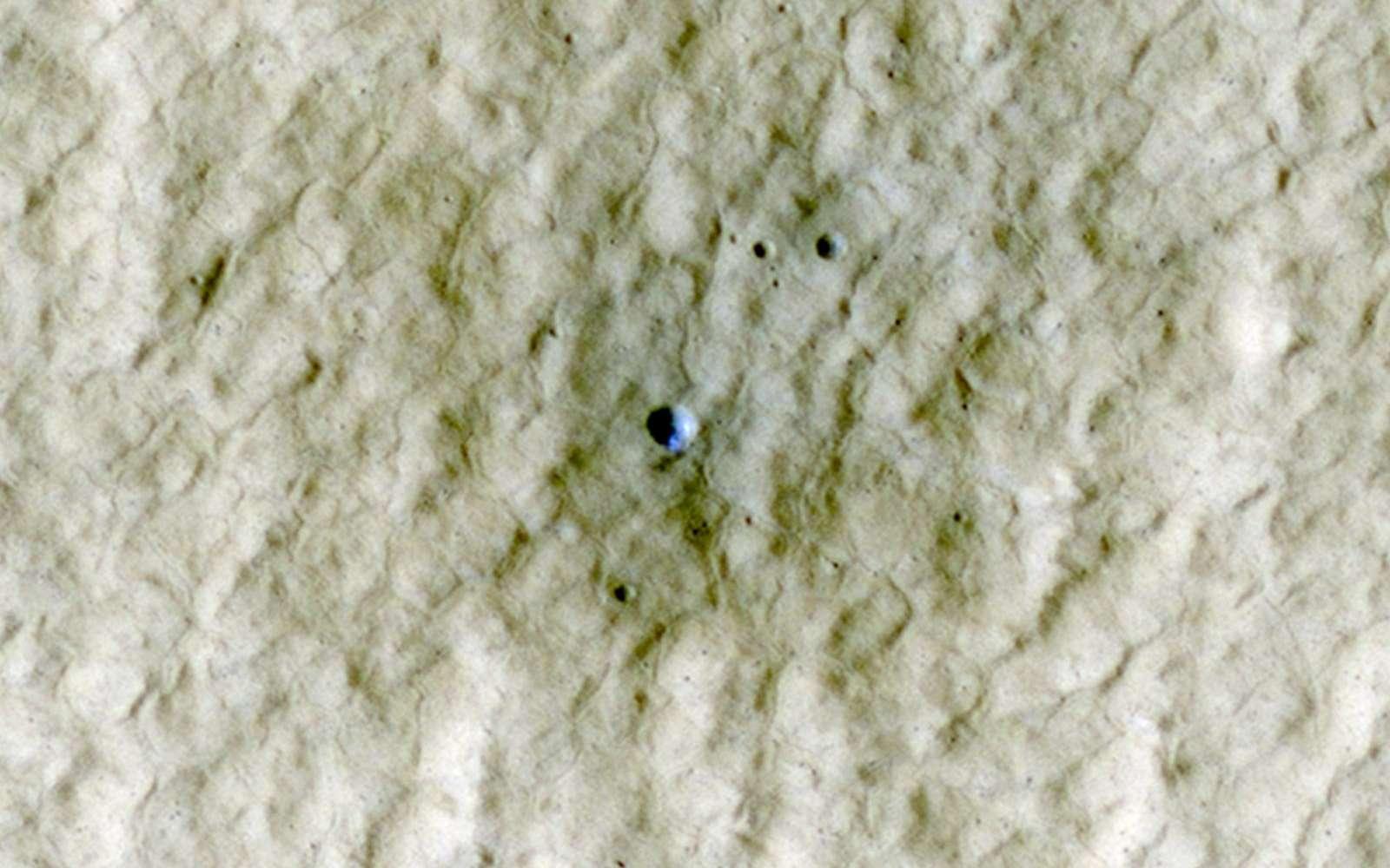 À l'intérieur de ce petit cratère de 6 mètres, formé entre 2004 et 2010, on aperçoit (en fausses couleurs) de la glace d'eau, remontée du sous-sol à la suite de l'impact. © Nasa/JPL-Caltech/University of Arizona