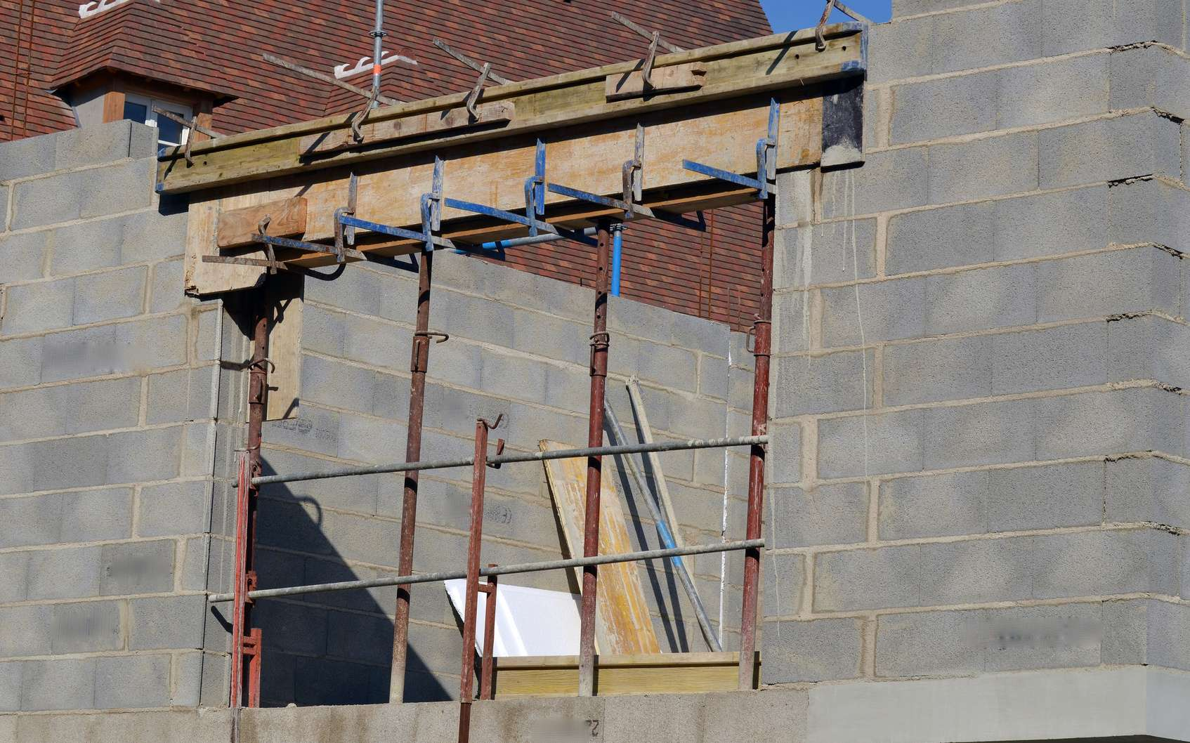 Que ce soit pour une fenêtre ou une porte, le coffrage d'un linteau coulé doit être solidement étayé et calé de niveau. Les planches sont huilées sur leur face intérieure afin de faciliter le décoffrage, après la prise du béton. © guidebeton.com