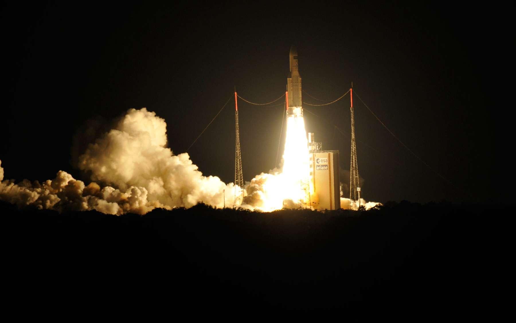 Ariane 5ES au décollage (en juillet 2014) avec le nuage de combustion qui se forme, issu du mélange entre les produits émis par les étages d'accélération à poudre et les eaux de déluge qui refroidissent les installations. © Rémy Decourt
