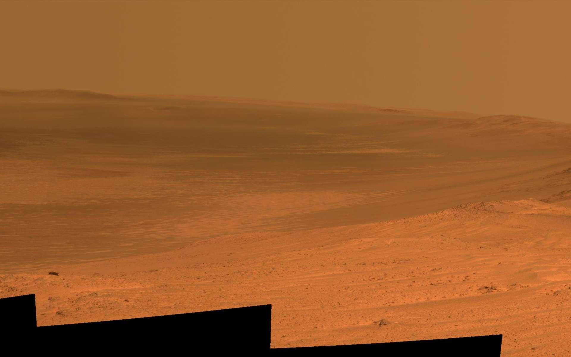 Mosaïque d'images prises le 18 avril 2014 (sol 3.637 de la mission) par la caméra panoramique (Pancam) d'Opportunity. Depuis la crête de Murray, au sommet des remparts ouest du vaste cratère d'impact, le rover profite d'un point de vue inédit sur les bordures est et sud-est d'Endeavour, distantes de 21 km. Beaucoup plus proche (environ 2 km), à droite de l'image, en direction du sud, se trouve son prochain site d'investigation, le Cap Tribulation. Au fond du cratère, on peut observer des dépôts de sables, de poussières et au lointain, un voile brumeux de poussières. © Nasa, JPL-Caltech, Cornell University, Arizona State University