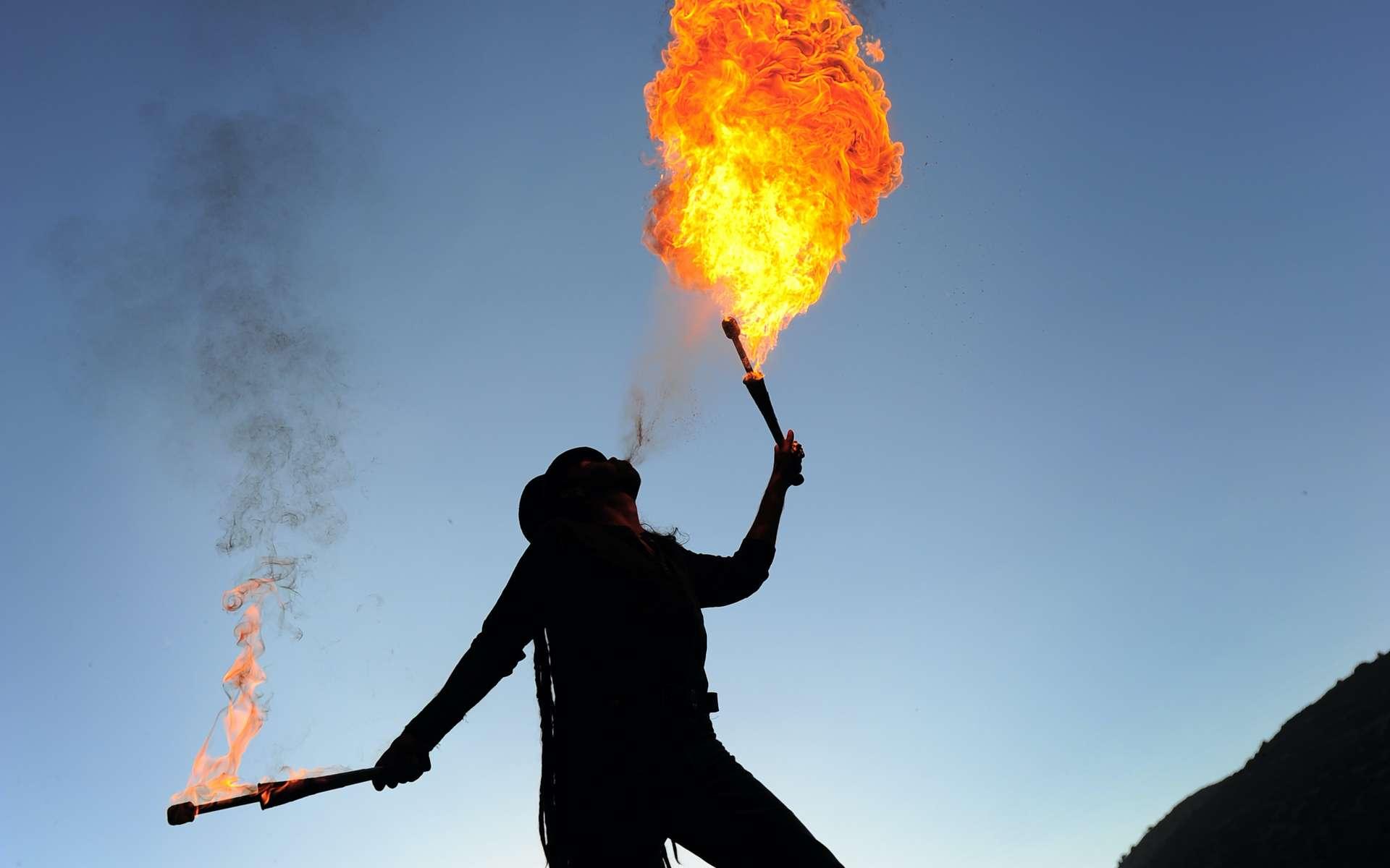 Le cracheur de feu vaporise le liquide inflammable sur une flamme, ce qui engendre des vapeurs qui s'enflamment et forment une boule de feu. © Rémy Masseglia, Adobe Stock