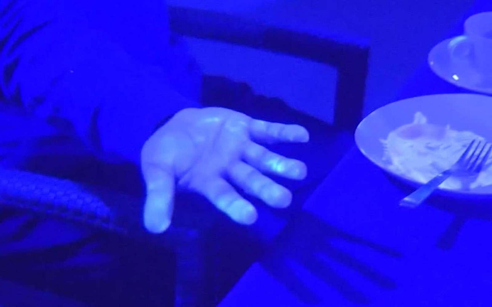 Grâce à la lumière noire, un média japonais met en évidence la propagation du coronavirus lors d'un repas partagé. © NHK News