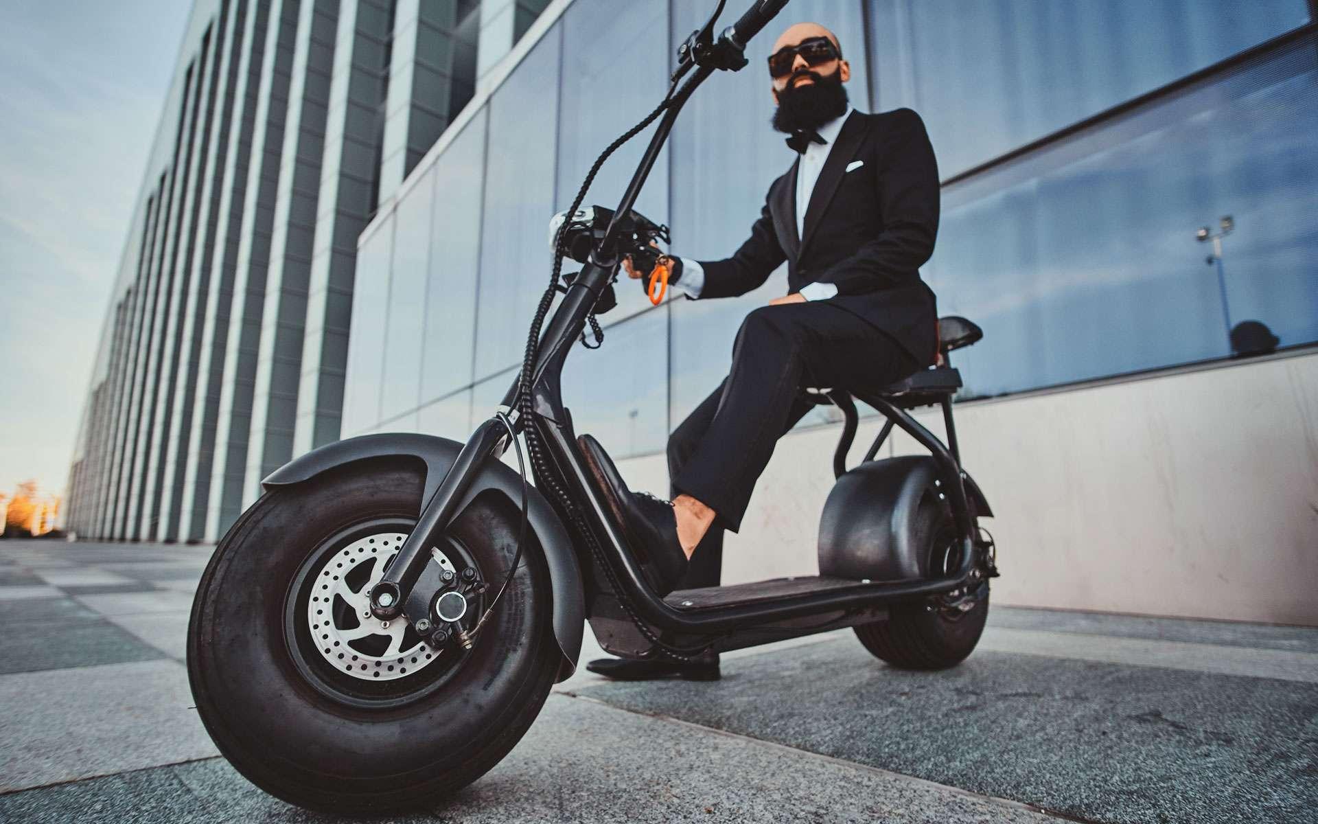 Un homme est installé son sur son deux roues électriques en bas de bureaux professionnels © fxquadro, Envato Elements