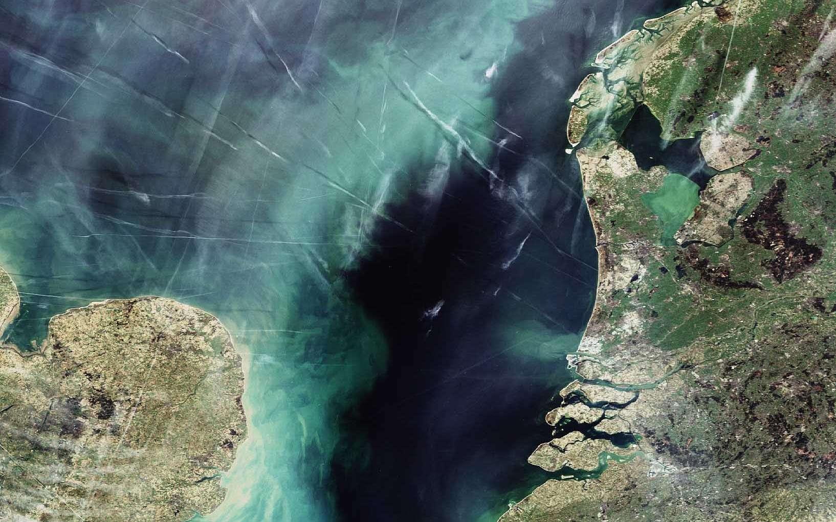 La Mer du Nord vue par Envisat. On y voit une partie des Pays-Bas (à droite), de la Belgique (en bas à droite) et de l'Angleterre (en bas à gauche). Elle laisse également apparaître de nombreuses traînées de condensation laissées par des avions. Crédit Esa/Envisat