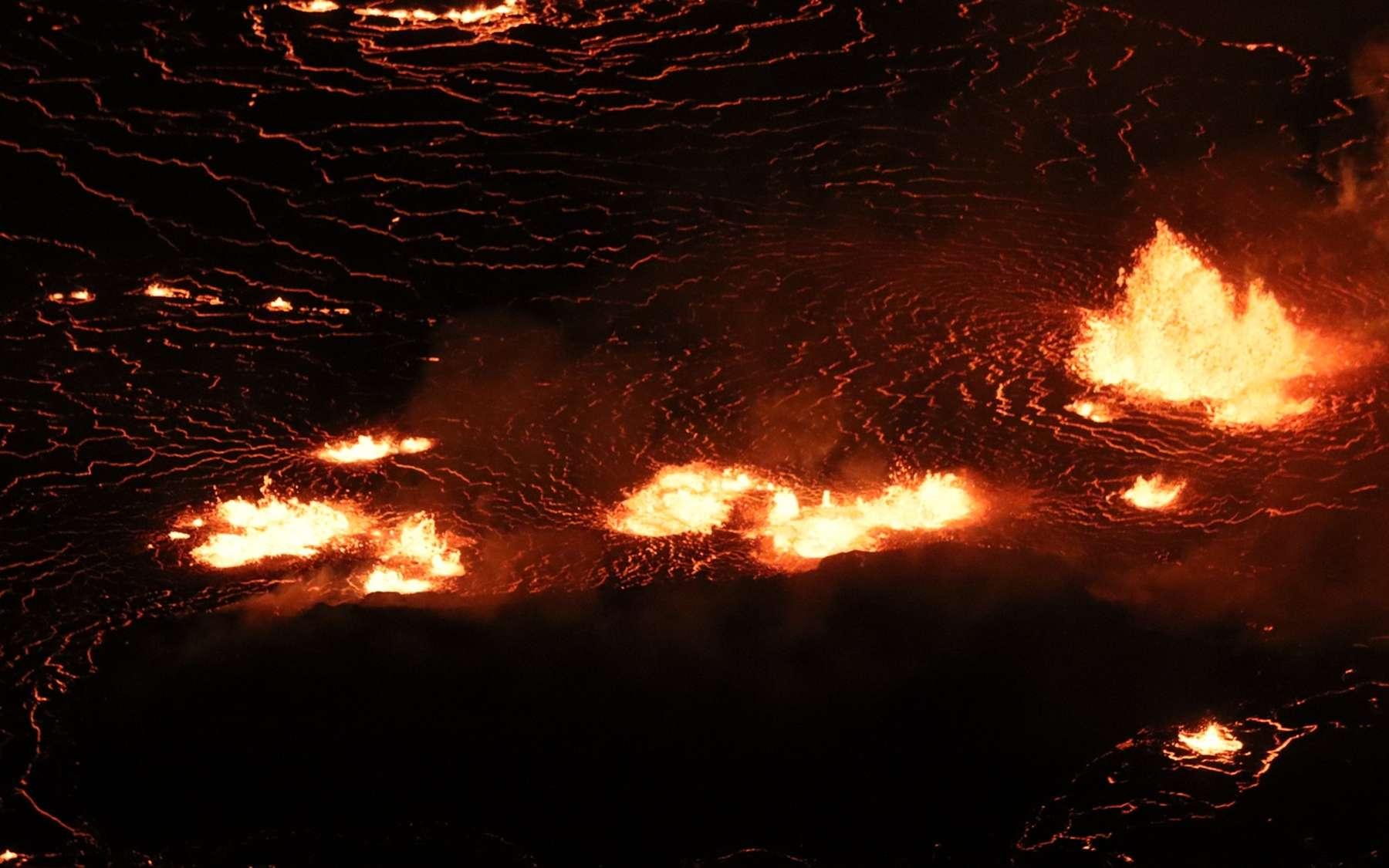 L'éruption en cours du sommet du Kīlauea dans le cratère Halema'uma'u continue d'alimenter les fontaines de lave basses au centre du lac de lave (photo) et le long du mur ouest du cratère Halema'uma'u. Cette image au téléobjectif regarde vers l'est au centre du lac de lave. La zone sombre sous les fontaines est « l'île de lave » qui s'est formée en décembre 2020. © USGS M. Patrick