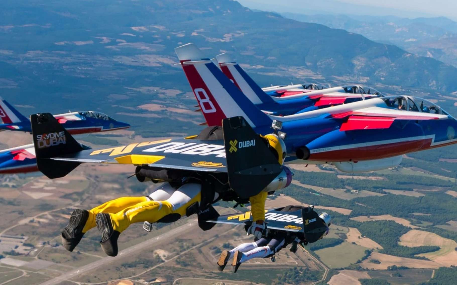Trois hommes équipés du jetpack d'Yves Rossy (dont lui-même) volent en patrouille avec les huit Alphajet de la Patrouille de France, en octobre 2016. © Airborne