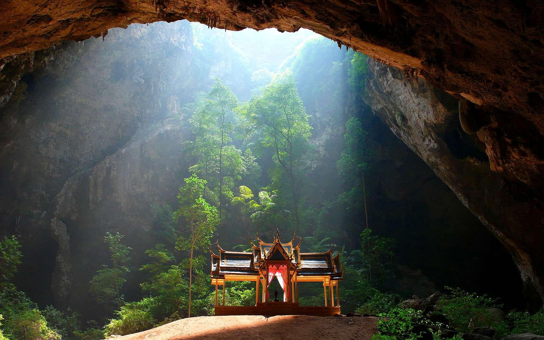 La grotte de Phraya Nakhon, en Thaïlande. Cette vue de la grotte de Phraya Nakhon située dans le parc national marin de Khao Sam Roi Yot, en Thaïlande, permet de découvrir un élégant pavillon dédié au roi Rama V, qui a été édifié sur un petit tertre d'argile rougeâtre. La vaste caverne de roche calcaire a été creusée par le ruissellement des eaux pluviales et sa partie supérieure est percée de plusieurs ouvertures au travers desquelles s'infiltre la lumière du jour. Une arche, sorte de pont fantasmagorique, surplombe la grotte dans laquelle croît une végétation luxuriante. © Niels Mickers, CC by 3.0 NL