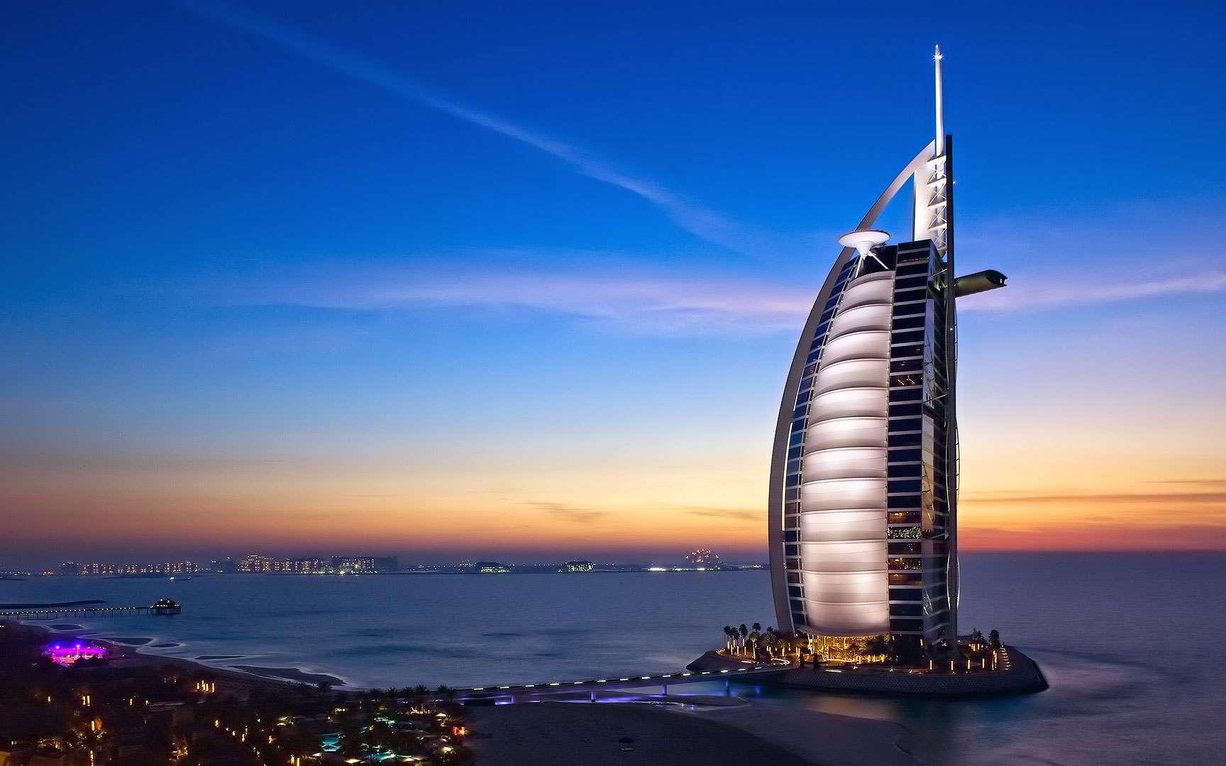 L'hôtel Burj al-Arab, à Dubaï, aux Émirats arabes unis. Le Burj al-Arab (en arabe la « tour des Arabes ») est un hôtel de luxe situé à Dubaï, aux Émirats arabes unis. C'est l'un des plus hauts hôtels du monde (321 mètres). Il est situé sur une île artificielle, à 280 mètres de la plage et a la forme d'une voile géante. Il a été construit de telle façon que son ombre ne recouvre pas la plage. © DR