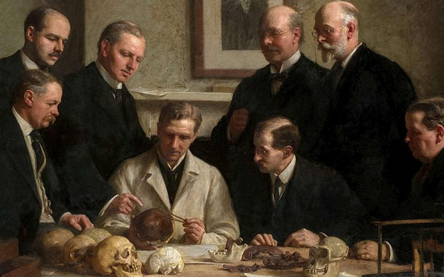 En 1915, le peintre John Cooke immortalise la découverte du crâne de Piltdown dans ce tableau où des scientifiques l'examinent avec attention. Charles Dawson et Sir Arthur Smith Woodward sont représentés, debout, à droite. © DP