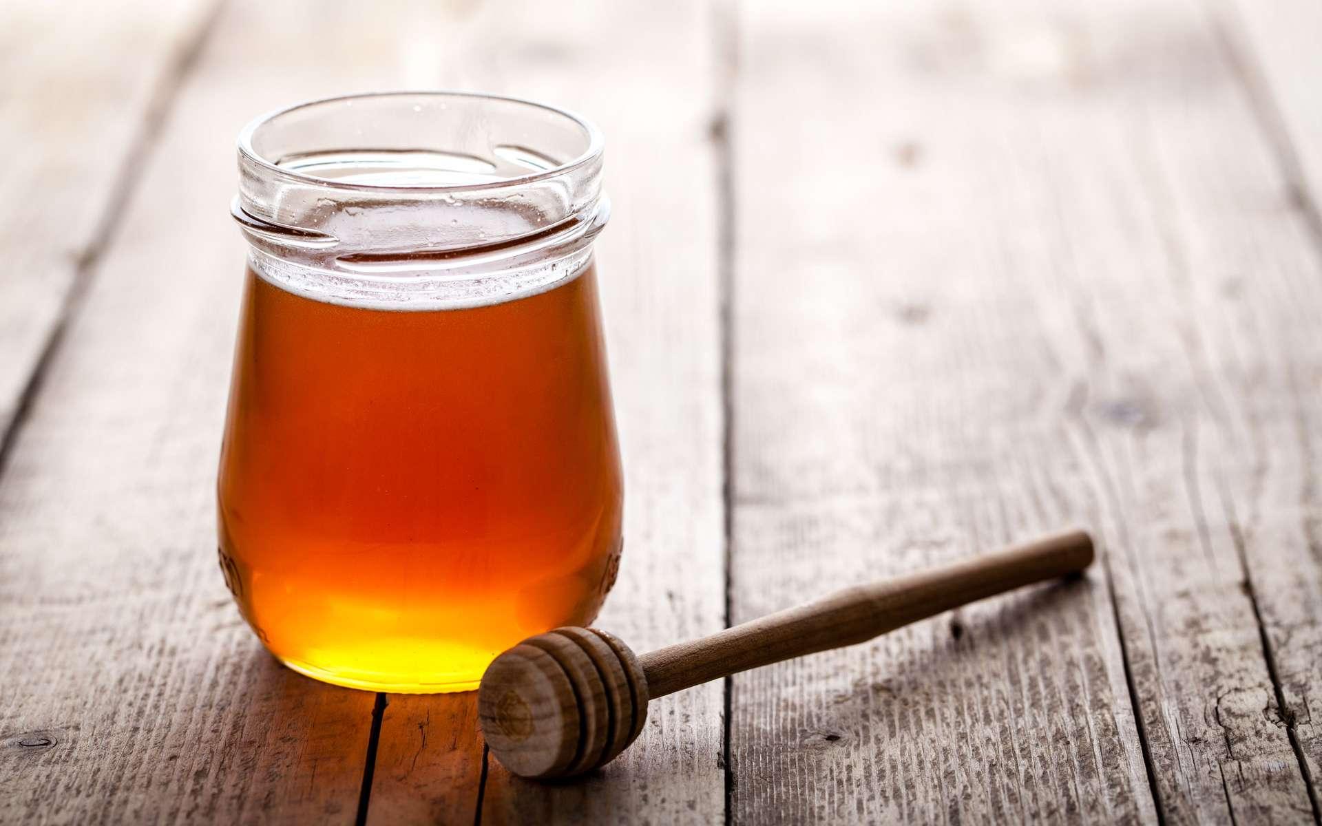 Un pot de miel posé sur une table avec une cuillère en bois ©serbogachuk