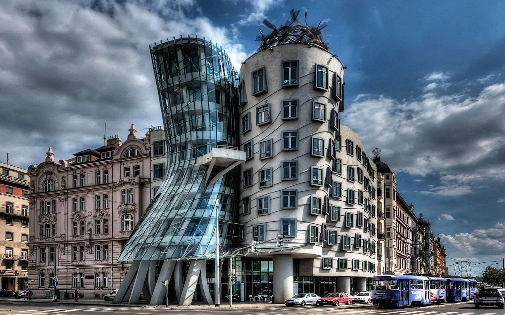 La maison dansante à Prague, par Vlado Milunić et Frank Gehry. La maison qui danse ou maison dansante a été réalisée conjointement par Vlado Milunić, un architecte tchèque d'origine croate et le Canadien Frank Gehry. Elle se trouve sur les quais de la rive droite de la rivière Vltava, au centre de Prague. La construction vit le jour sur l'idée de Vaclav Havel alors président de la République tchèque, après la Révolution de velours. Il souhaitait en faire un centre culturel mais le bâtiment fut racheté par le bancassureur néerlandais ING qui laissa le projet à Vlado Milunic à la condition qu'il s'adjoigne le concours d'un architecte de renommée internationale. Frank Gehry accepta la collaboration et ING leur fournit un budget illimité pour finaliser le projet. Les deux tours enlacées simulant un couple de danseurs en fait un immeuble inattendu à l'indéniable effet poétique. © Pedro Szekely, CC by-sa 2.0