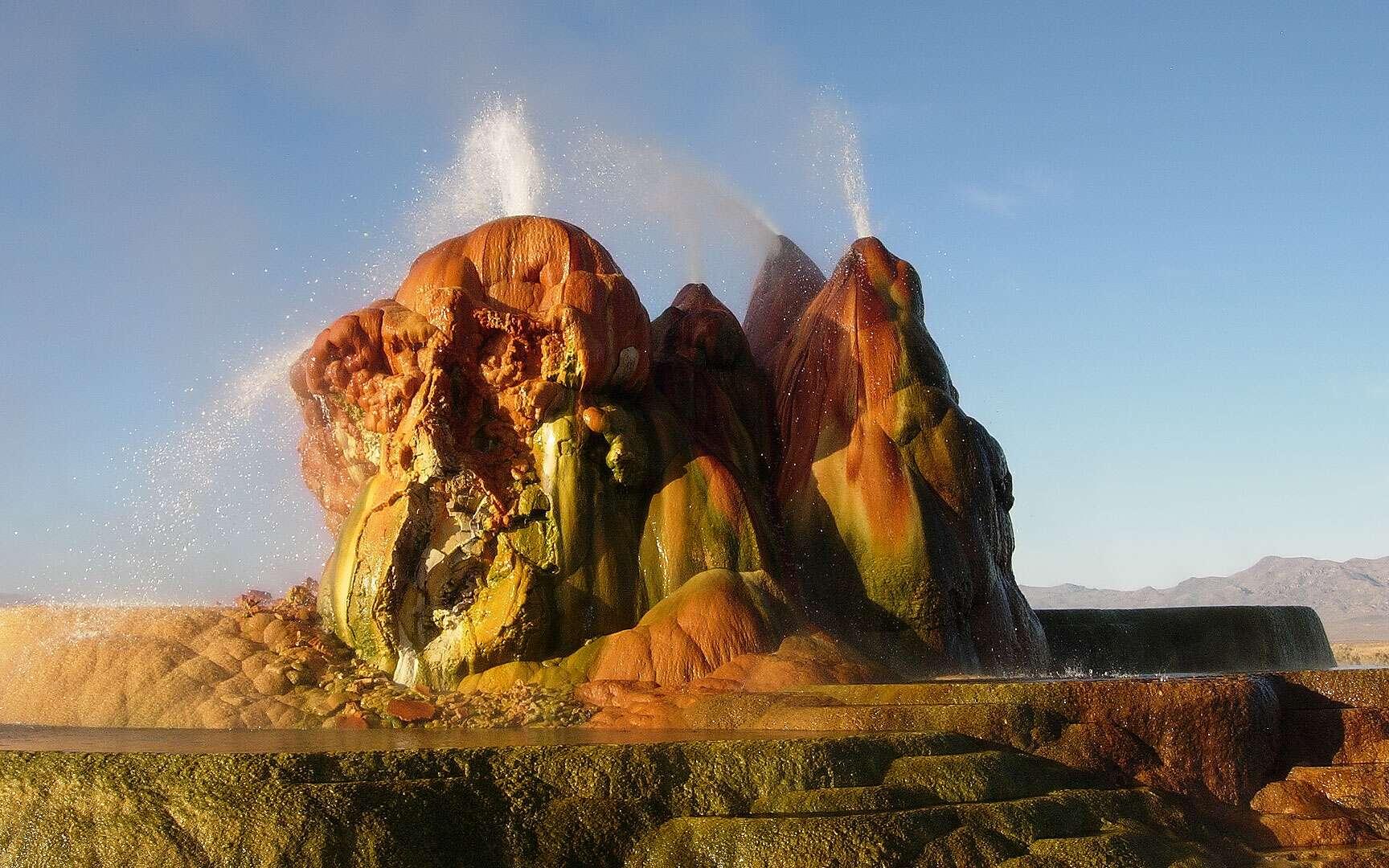 Le Fly Geyser dans le Nevada, aux États-Unis. Le Fly Geyser, aussi connu comme le Fly Ranch Geyser, se trouve dans le désert de Black Rock, au Nevada (États-Unis). Ce geyser n'est pas vraiment naturel. Il est apparu vers 1964 suite au forage d'un puits cinquante ans auparavant. Le puits n'ayant pas été correctement façonné, une source géothermique s'est infiltrée et les minéraux dissous se sont peu à peu empilés pour former ce monticule composé de trois cônes de couleur rouge-orange qui crachent de l'eau en permanence. © Ken Lund, CC by-sa 2.0