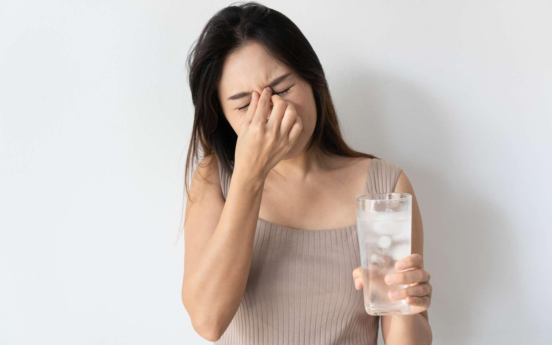 Jeune femme ressentant un terrible mal de tête ou « brain freeze » après avoir bu un verre d'eau glacé. © Pattarisara, Adobe Stock