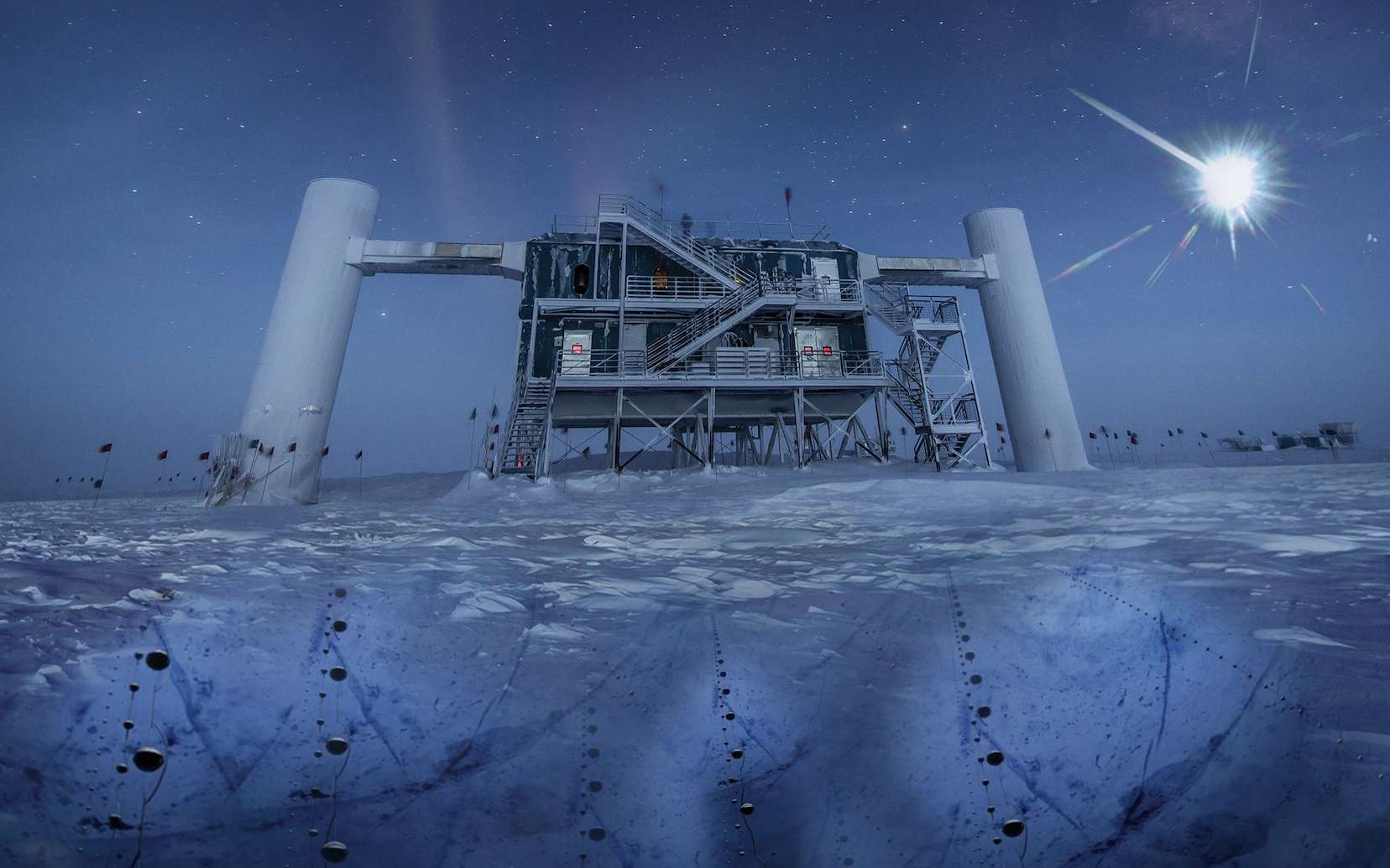 Une vue des bâtiments de surface du détecteur géant de neutrinos IceCube, en Antarctique. La pureté de la glace à plus d'un kilomètre de profondeur permet à plus de 5.000 photomultiplicateurs d'enregistrer avec précision les flashs bleutés très ténus générés par les muons issus de la collision des neutrinos avec les noyaux atomiques dans la glace. La construction de IceCube a commencé en 2005, mais le détecteur est une version plus grande d'Amanda, qui date du début des années 1990. © Felipe Pedreros, IceCube, NSF