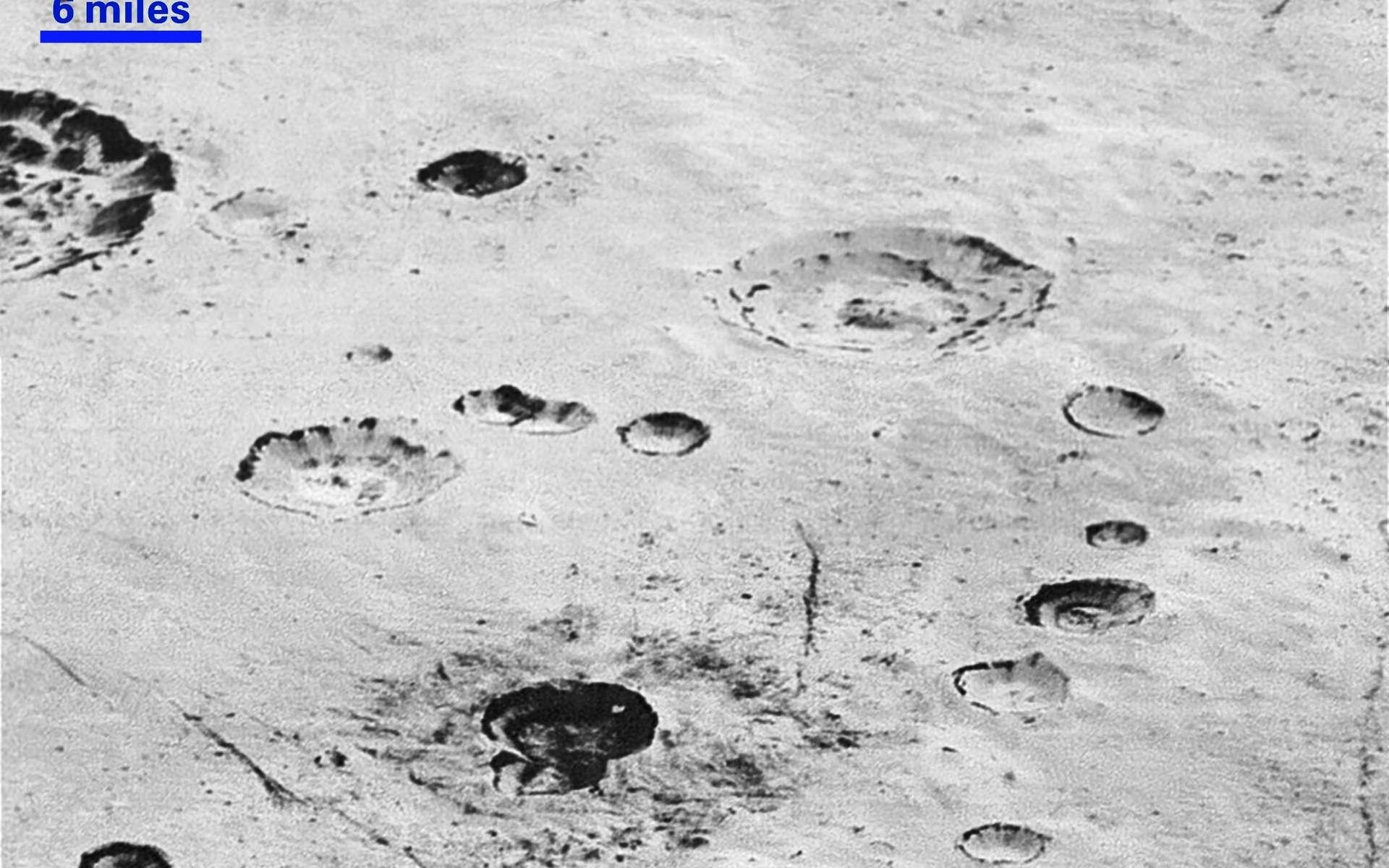 Cette image à haute résolution montre la structure stratifiée des parois de cratères d'une plaine glacée de Pluton. Sur Terre, elle indiquerait une activité géologique. Ici, il est difficile de dire s'il s'agit d'évènements locaux, régionaux ou globaux. Les structures linéaires sombres en bas de l'image pourraient trahir une tectonique. La majorité des cratères visibles se trouvent dans le bassin Burney, large d'environ 250 kilomètres (son nom honore Venetia Burney, l'écolière anglaise de 11 ans qui a proposé le nom de Pluton pour la nouvelle planète découverte en 1930). La barre en haut à gauche donne l'échelle : 6 miles correspondent à environ 9,6 kilomètres. © Nasa, JHUAPL, SwRI