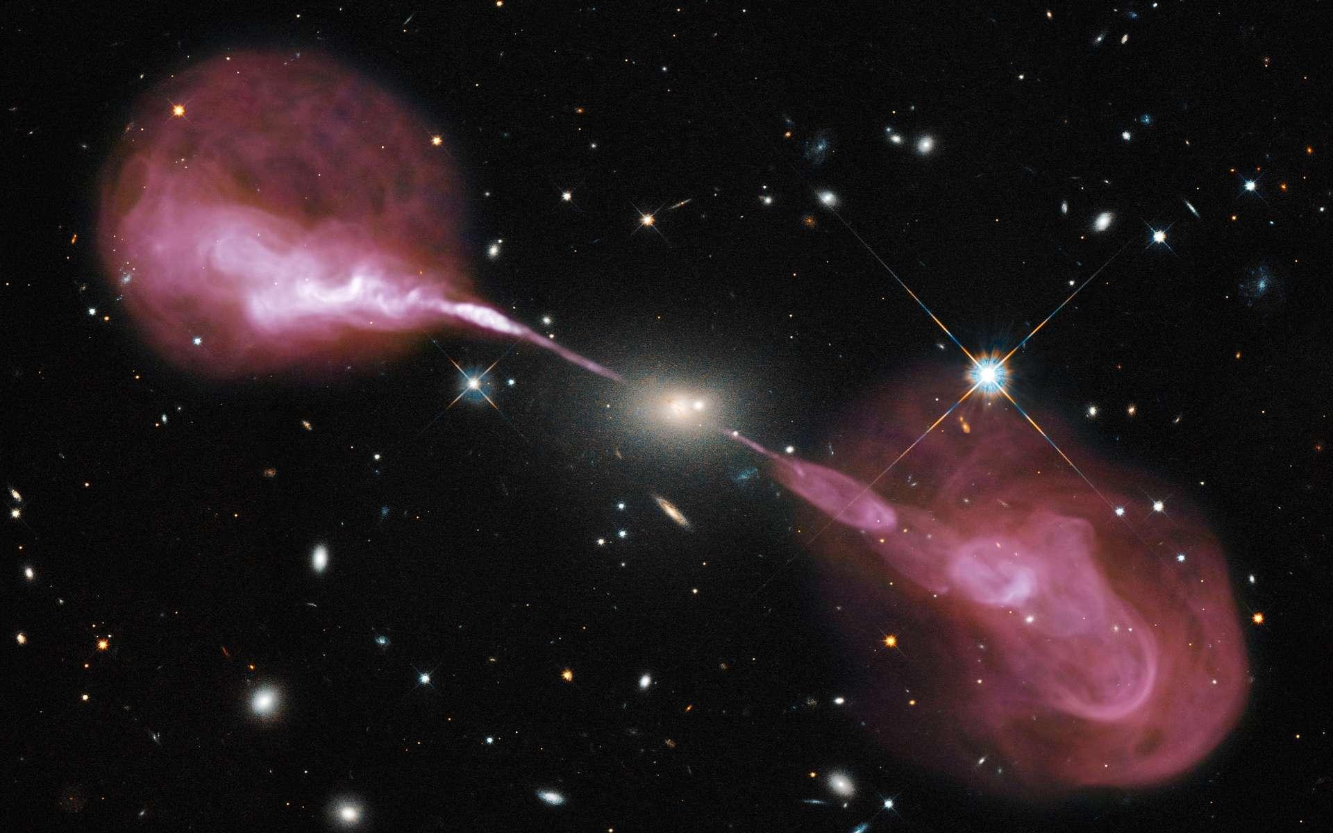 Hercules A est une galaxie elliptique située à environ 2 milliards d'années-lumière de la Voie lactée. Environ 1.000 fois plus massive que notre Galaxie, elle abrite un trou noir central de 2,5 milliards de masses solaires. On la voit dans le visible sur cette photographie prise par Hubble et sur laquelle a été surimposée une image réalisée dans le domaine des ondes radio par le VLA. Se révèlent alors deux lobes radio produits par des jets de matière relativistes, longs de plusieurs millions d'années-lumière. © Nasa, ESA, S. Baum and C. O'Dea (RIT), R. Perley and W. Cotton (NRAO/AUI/NSF), and the Hubble Heritage Team (STScI/AURA)